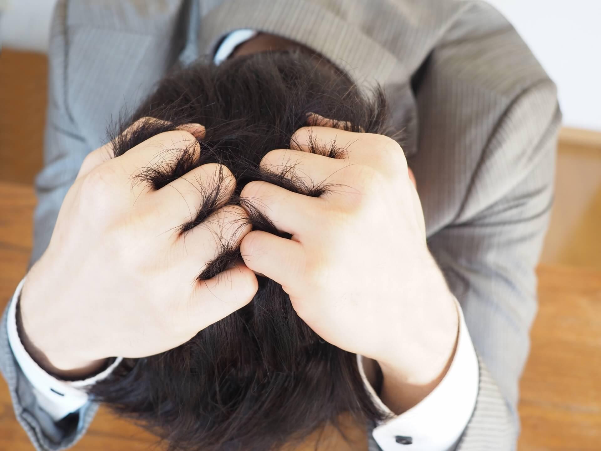 仕事で疲弊しミスをして頭を抱える男性