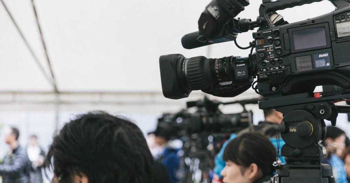 テレビの記者会見に集まるカメラ